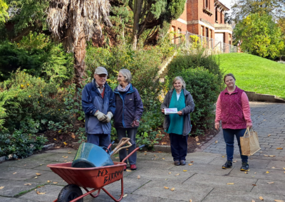 The volunteers of Sudbury Gardens pose in front of their work at the gardens