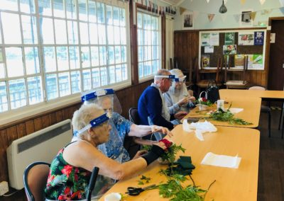 Four members of the Elderflower Hub sit at a table and make floristry baskets