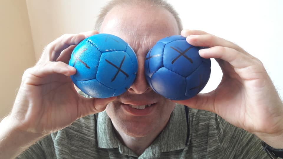 A Boccia player holds blue boccia balls to his eyes to make him look like he has 2 giant big blue eyes.