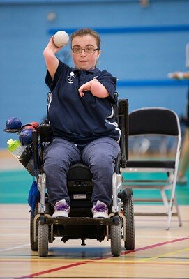 Evie Edwards, Paralympian, holds a ball in her right hand and aims a shot during a Boccia game at an ActivLives session.