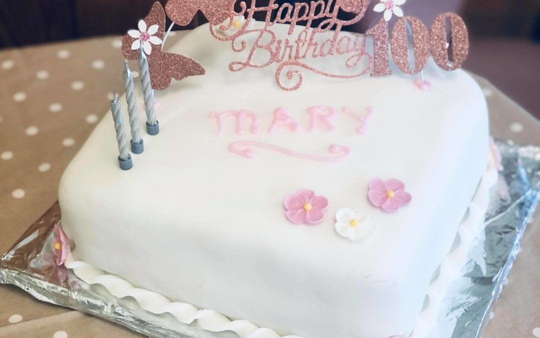 A photo of Mary's 100th birthday cake. Three cancdles stand on top of a white iced cake with a cake decoration that says happy 100th birthday.