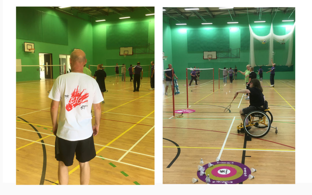 On the left hand side of the image a man stands with his back to the camera wearing a Big Hit t-shirt on the right of the image Donna, a wheelchair user plays badminton